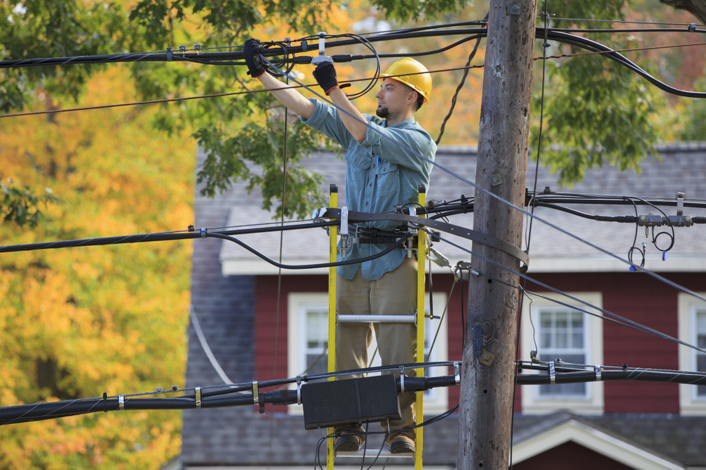 Lineman working on cables at power pole.